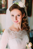 Close up portrait of happy stylish bride in luxury white dress and veil posing with pink rose near the window Stock Photos