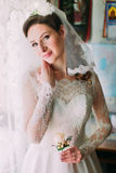 Close up portrait of happy stylish bride in luxury white dress and veil posing with pink rose near the window Royalty Free Stock Images