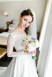 Close up portrait of happy stylish bride in luxury white dress and veil posing with pink roses near the window.  Royalty Free Stock Images