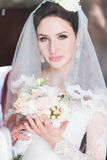 Close up portrait of happy stylish bride in luxury white dress and veil posing with pink roses near the window.  Stock Image
