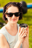 Close-up portrait of happy woman with sunglasses and coffee Stock Images