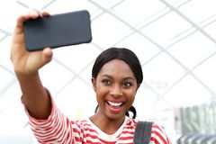 Close up happy young african american woman taking selfie and laughing royalty free stock photography