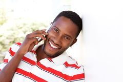 Happy young man leaning to wall and talking on cell phone Stock Photo