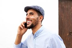 Close up happy young arabic man talking on mobile phone stock photos