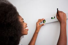 Close up happy young black woman drawing straight line on wall royalty free stock image