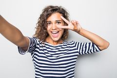 Close up portrait of a happy young curly mulatto woman making selfie against isolated white background stock photography
