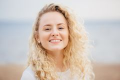 Close up portrait of happy young cute female with curly hair, looks gladfully directly at camera, has broad smile, poses against s stock images