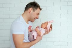 Close-up portrait of happy young father hugging and kissing his sweet adorable newborn child. Happy Family concept royalty free stock images