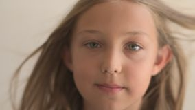 Close Up Portrait of happy young  girl with blue eyes and blond hair. Standing on Wind. Breeze is playing with girl`s hair. Stormy stock video
