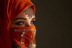 Studio shot of a young charming woman wearing the terracotta hijab decorated with sequins and jewelry. Arabic style. stock photos