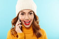 Close up portrait of a happy young girl. Dressed in winter clothes talking on mobile phone and looking at camera isolated over blue background Stock Images