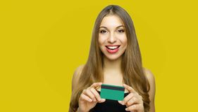 Close up portrait of happy young girl with long hair showing credit card isolated over yellow background stock images