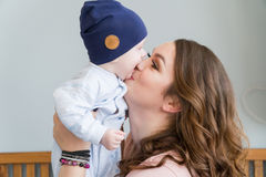 Close-up portrait of happy young mother hugging and kissing his sweet adorable child. Indoors shot, concept image Stock Image