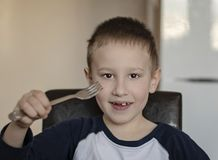 Close-up portrait of happy young pre-school boy eating with a fork in the kitchen at home stock image