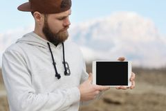 Close-up Portrait of a hipster in a brown cap in the open air holds a white tablet pc in his hands. A bearded man looks royalty free stock photos
