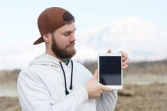Close-up Portrait of a hipster in a brown cap in the open air holds a white tablet pc in his hands. A bearded man looks stock photo