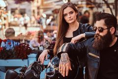 Close-up portrait of a hipster couple - bearded brutal male in sunglasses dressed in a black leather jacket and his. Young sensual girl standing near, posing Royalty Free Stock Images