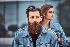 Close-up portrait of a hipster couple of a brutal bearded male and his girlfriend dressed in jeans jackets against royalty free stock images