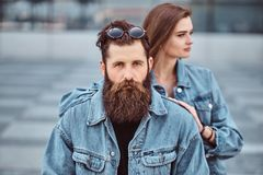 Close-up portrait of a hipster couple of a brutal bearded male and his girlfriend dressed in jeans jackets against stock photography