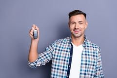 Close-up portrait of his he nice attractive confident content cheerful cheery bearded guy holding in hand remote lock. Close-up portrait of his he nice royalty free stock photography