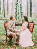 The close-up portrait of the holding hands newlyweds and sitting on the stylish soft chairs between the hanging stump. With the green strawberry cake on it. The Stock Image