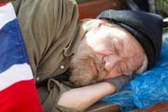 Close up portrait of homeless man sleeping on bench in city park. Poor aold male with no home and money living in the streets Stock Images
