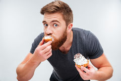 Close up portrait of a hungry man biting cream cake royalty free stock photo
