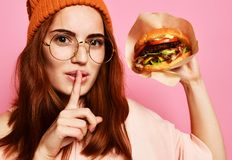 Close up portrait of a hungry young woman eating burger isolated over pink background stock photos