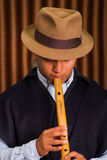 Close up portrait of indigenous young man playing the quena flute Royalty Free Stock Photo