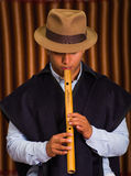 Close up portrait of indigenous young man playing the quena flute Stock Image