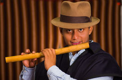 Close up portrait of indigenous young man playing the quena flute Royalty Free Stock Photos