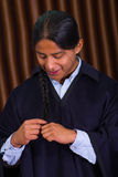 Close up portrait of indigenous young man weaving his hair on a braid Stock Photos
