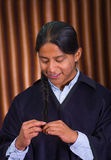 Close up portrait of indigenous young man weaving his hair on a braid Stock Images