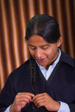 Close up portrait of indigenous young man weaving his hair on a braid Stock Photography