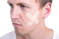Close up portrait of injured man with adhesive plaster on his cheek Royalty Free Stock Photography