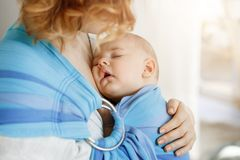 Close up portrait of innocent newborn boy having sweet dreams on mother chest in baby sling. Mom looking at her child royalty free stock photo