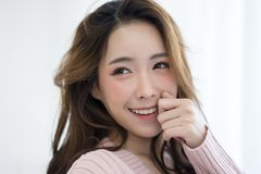 Close-up portrait of inspired caucasian Asian lady wearing knitted sweater pink cold smilling and taking selfie. Isolated white b stock photography