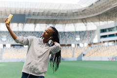 Close-up portrait of the joyful afro-american girl in the earphones touching the hair while taking selfie at the. Nackground of the stadium Stock Images