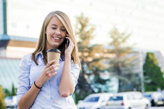 Close up portrait of a joyful businesswoman using her smartphone. And carrying work folders, standing against a sunny blue sky Stock Photo