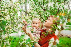Mother and daughter in flower garden. Close up portrait of a joyful mother and daughter relaxing together in a beautiful spring field of grass and flowers Stock Photo