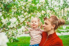 Mother and daughter in flower garden. Close up portrait of a joyful mother and daughter relaxing together in a beautiful spring field of grass and flowers Royalty Free Stock Images