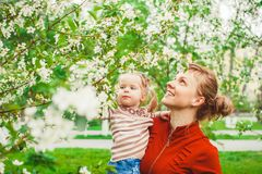 Mother and daughter in flower garden. Close up portrait of a joyful mother and daughter relaxing together in a beautiful spring field of grass and flowers Stock Images