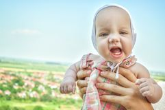 Close up. Portrait of a laughing baby with first teeth, against a background of mountain nature royalty free stock photo