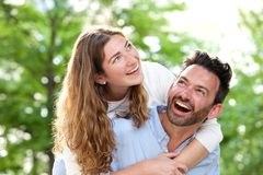 Portrait of laughing boyfriend carrying beautiful girlfriend outside in park Royalty Free Stock Photos