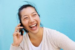 Laughing asian woman talking on cell phone against blue wall Stock Photography