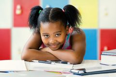 Tedious little african student sitting at desk in classroom. Stock Image