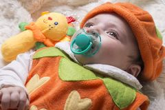 Close-up portrait of a little baby girl with pacifier lying on f Stock Images