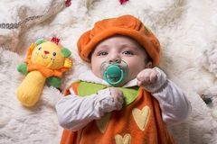 Close-up portrait of a little baby girl with pacifier lying on f Stock Photography