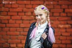 Close up portrait of little beautiful stylish kid girl near red brick wall as background stock photo