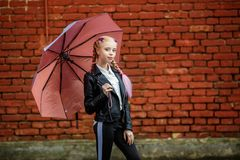 Close up portrait of little beautiful stylish kid girl with an umbrella in the rain near red brick wall as background stock photo